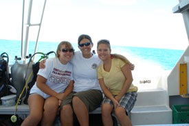 three friends enjoying the boat ride back in from the dive
